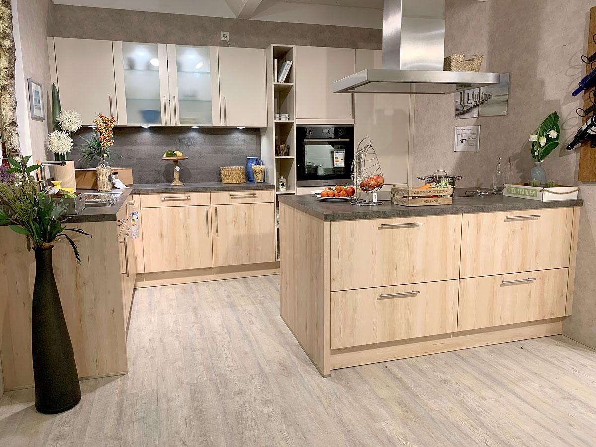 Elegante Einbauküche in L-Form mit Kochinsel in Champagnerfarbenen Fronten und schlichten Edelstahl-Stangengriff