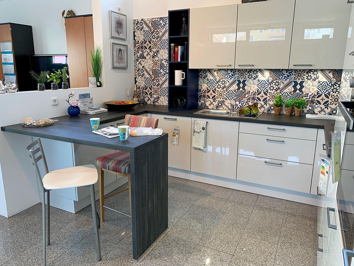 Moderne Winkelküche in Lacklaminat Kristallgrau hochglanz, mit Bartresen in Castelleiche Anthrazit. Besonderer Eyecatcher ist die Nischenverkleidung mit blauem Fliesendekor.